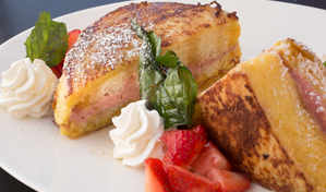 Savory brunch cuisine with strawberries on a white platter at Splashes