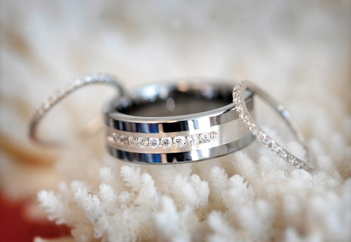 Slim diamond Rings on either side of a wider band on top white coral at our Laguna beach wedding hotel