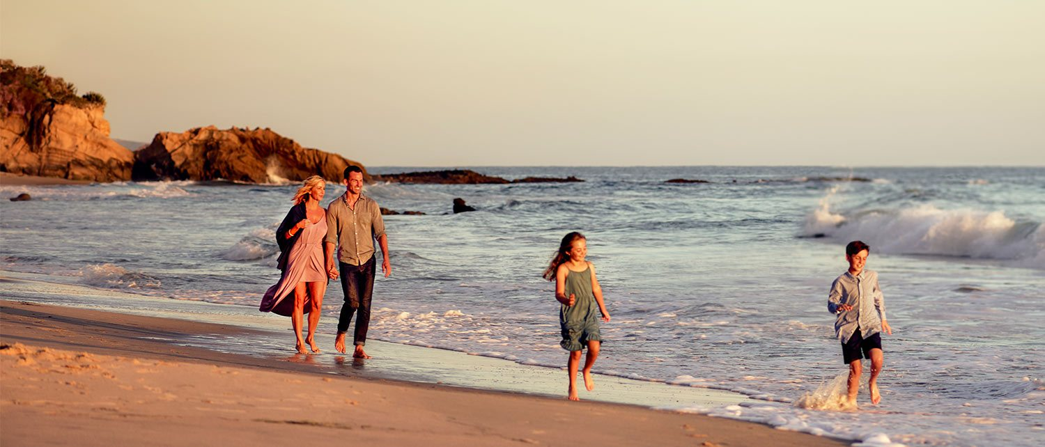 Family of four walking by the water at Surf and Sand Resort a beachfront hotel
