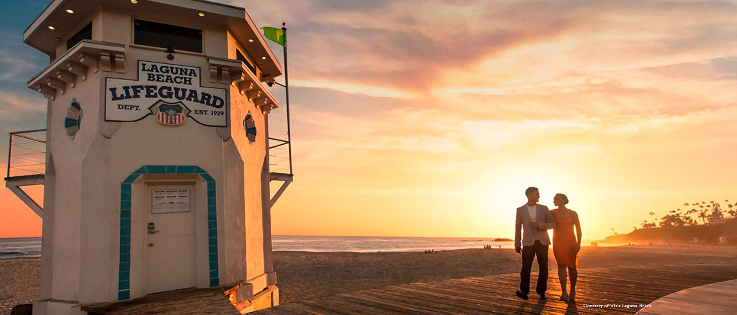 Couple walking down by the beach passing a Laguna Beach Lifeguard stand near Surf and Sand