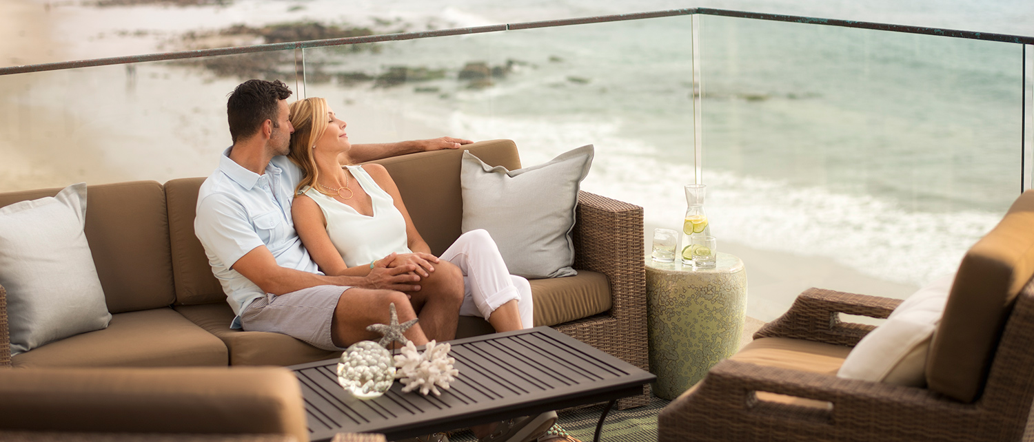 Couple relaxing above the Laguna Beach at our luxury hotel's deck with wicker furniture.
