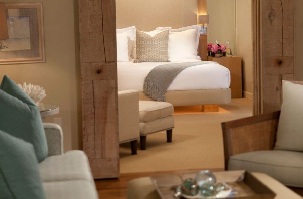 King guestroom featured through double doors from sitting area at our beachfront hotel in So Cal