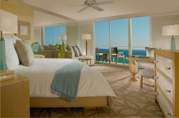Our beachfront hotel's king guest room with ocean views and balcony with chairs in So. California