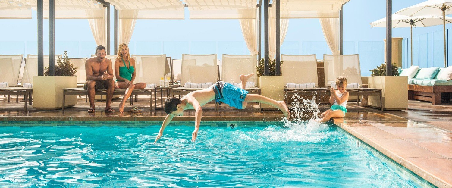 Family of four by pool, Boy jumping in girl on the edge at our beachfront hotel in Southern California