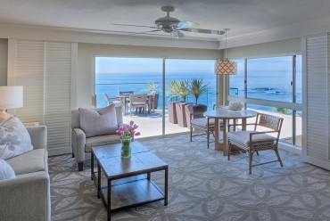 Laguna Beach accommodations living area with large couch, double sliding doors, deck with table & ocean views