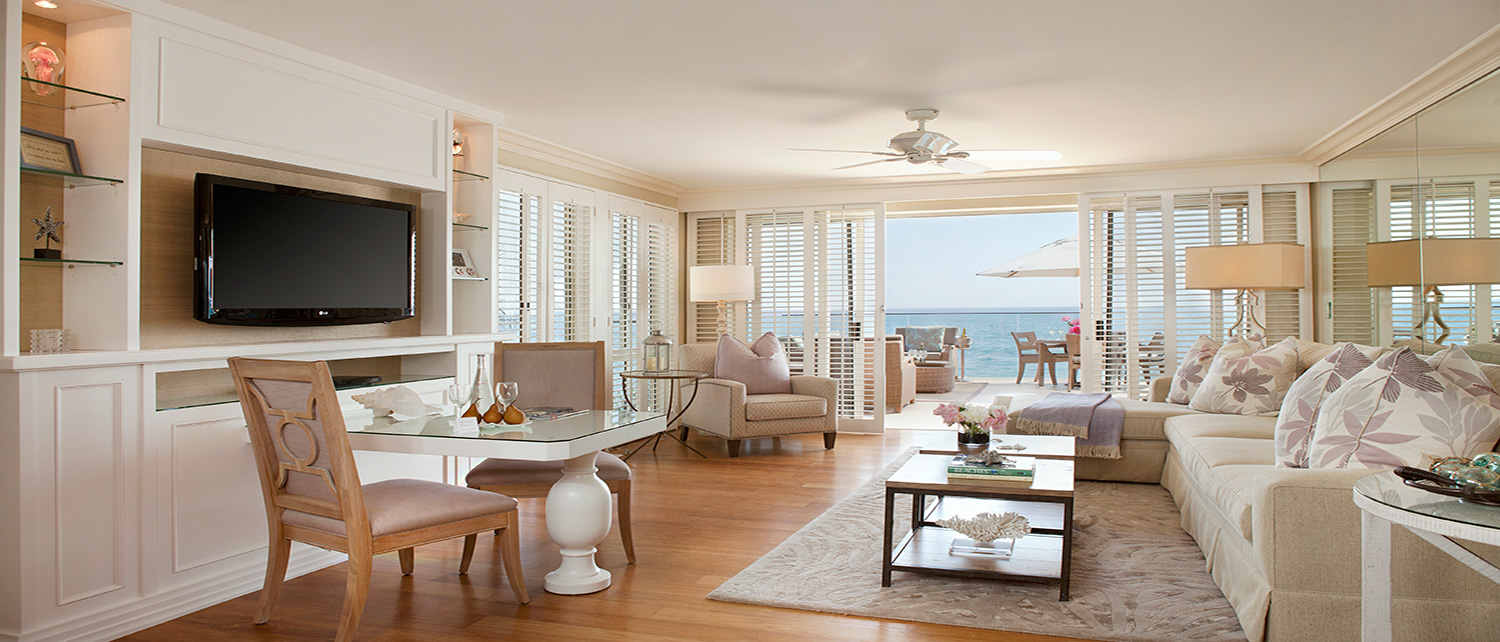 Vista Suite Living Space with L-shaped couch and large open balcony facing the ocean.
