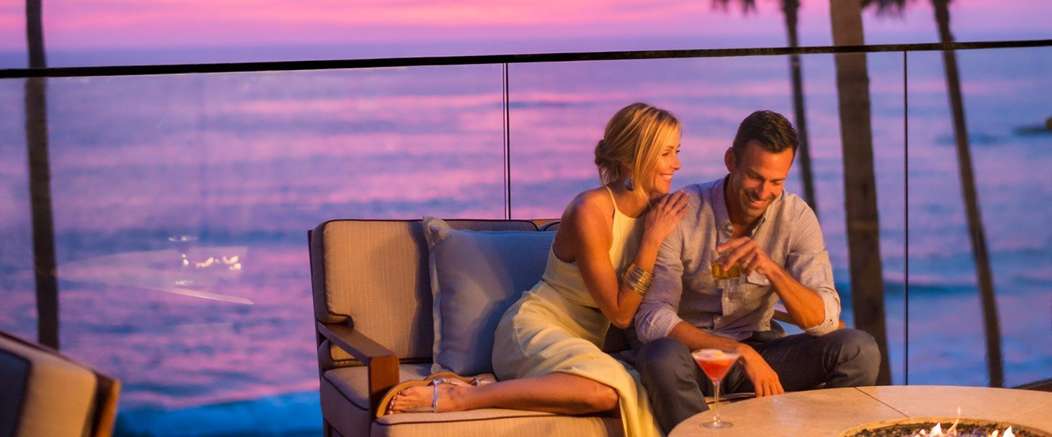 Couple sitting by firepit at sunset at 15fiftyfive Lounge at Surf & Sand Resort