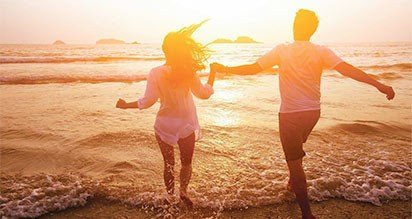 Couple running into the water at sunset at our beachfront hotel in Southern California