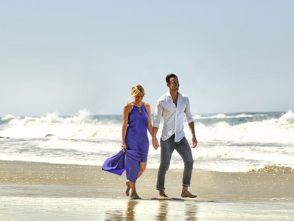 Couple walking along the pristine Pacific coastline in front of Surf & Sand Resort