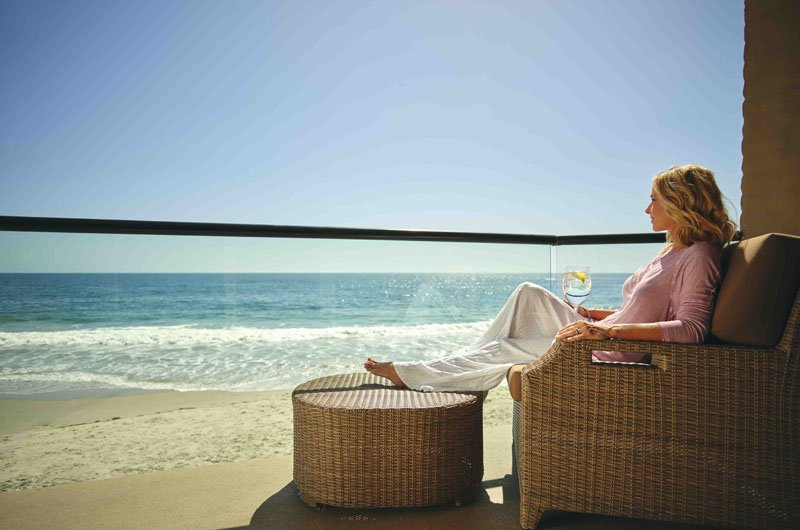Woman sitting in balcony at Surf & Sand Resort