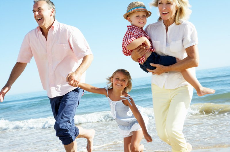 Grandparents And Grandchildren Enjoying Holiday Running Along Beach Smiling