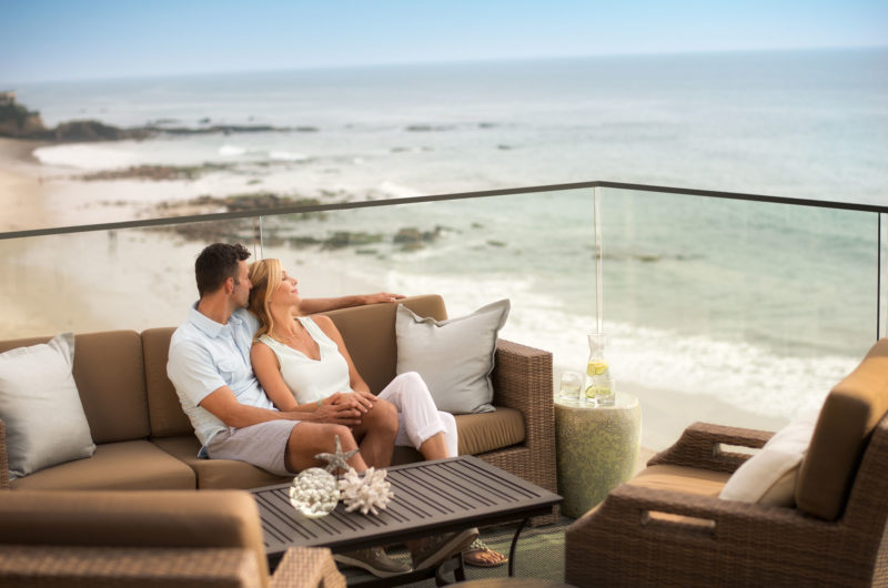 Couple relaxing on our balcony at our luxury beachfront resort, Surf and Sand